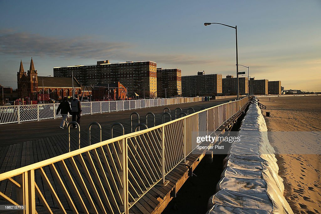 People walk on a section of boardwalk recently repaired at Rockaway Beach following the devastation of Hurricane Sandy which destroyed large parts of...