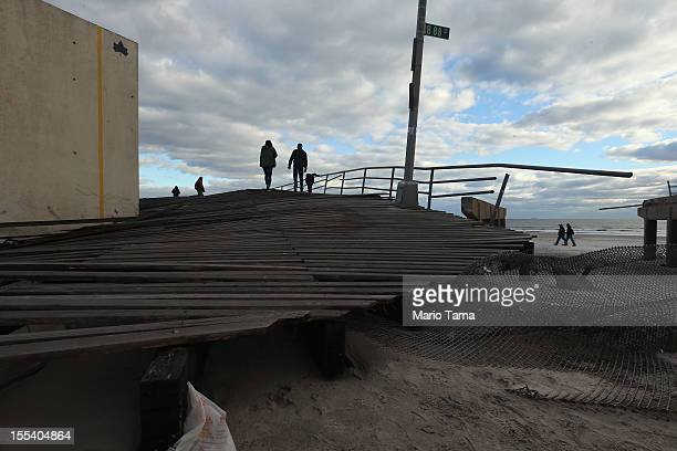 People walk on a small remaining section of the destroyed boardwalk following Superstorm Sandy at Rockaway Beach on November 3 2012 in the Queens...