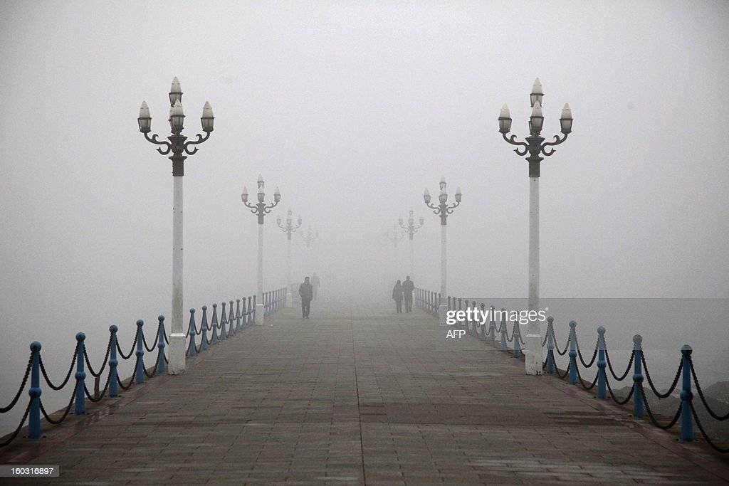 People walk on a smog-covered road in Qingdao, east China's Shandong province on January 29, 2013. Residents across northern China battled through choking pollution on January 29, as air quality levels rose above index limits in Beijing amid warnings that the smog may not clear until January 31. CHINA