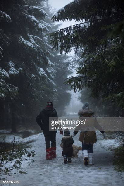 People walk on a snow covered road Signal de Botrange on November 12 2017 / AFP PHOTO / BELGA / KOEN BLANCKAERT / Belgium OUT