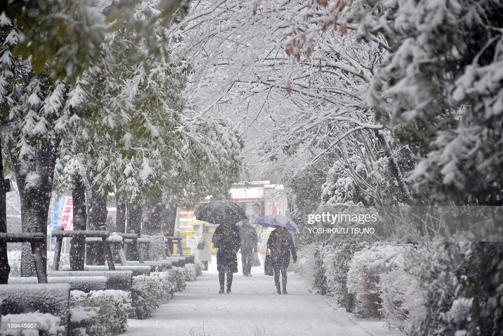 People walk on a snow covered street in Tokyo on January 14, 2013. A storm system grasped central Japan on January 14, causing heavy snow fall around the Japanese capital. AFP PHOTO / Yoshikazu TSUNO