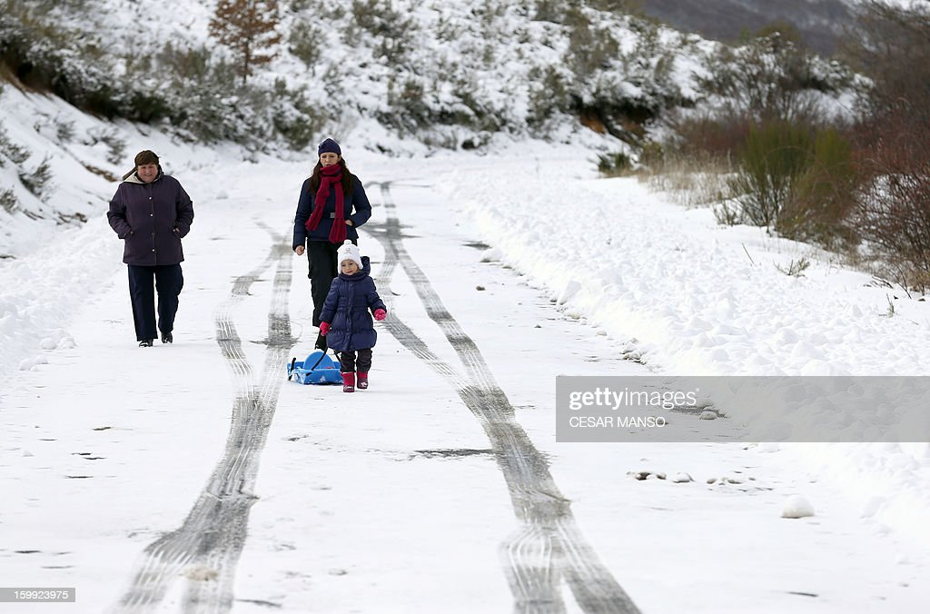 People walk on a snow-covered road in Pineda de la Sierra, near Burgos, on January 23, 2013. AFP PHOTO/ CESAR MANSO