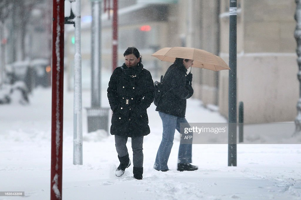 People walk on a snowy sidewalk, on March 12, 2013 in Caen, northwestern France, during a heavy snow storm on France. Overnight Monday nearly 500 cars were blocked near Cherbourg where snowdrifts piled up 60 centimetres (almost two feet) as winds reached 100 kilometres (more than 60 miles) an hour. Twenty-six regions in northwest and northern France were put on orange alert because of heavy snowfalls, which Meteo France said were 'remarkable for the season because of the expected quantity and length of time'.