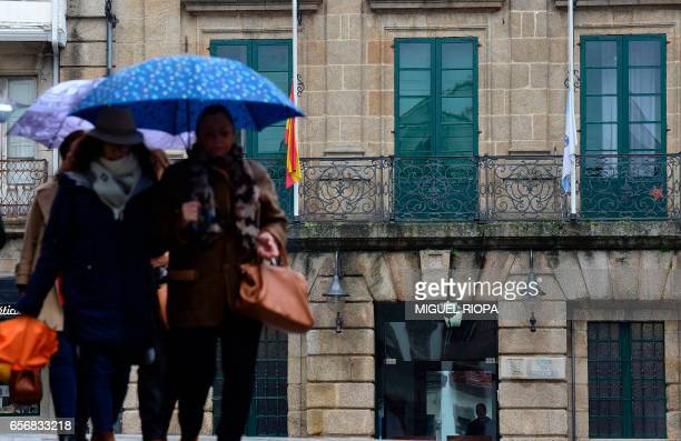 People walk on a sqaure with in background the Spanish flag and a local flag at half mast on a balcony of the council of Betanzos northwestern Spain...