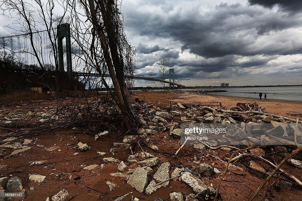 People walk on a still-closed beach damaged by flooding from Hurricane Sandy not far from the Verrazano-Narrows Bridge March 1, 2013 in the Staten Island borough of New York City. A government plan to purchase properties damaged by the storm remains on track.