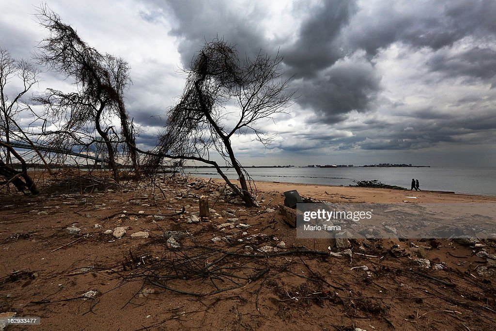 People walk on a still-closed beach damaged by flooding from Hurricane Sandy on March 1, 2013 in the in Staten Island borough of New York City. A government plan to purchase properties damaged by the storm in Staten Island remains on track.