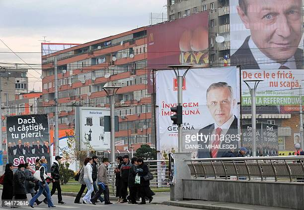 People walk on a street backdropped by electoral bilboards of Social Democratic Party's candidate Mircea Geoana and Romania's incumbent President...