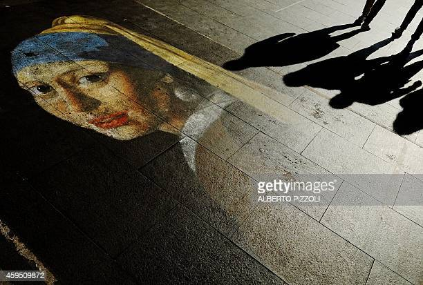 People walk on a street drawing depicting the 'Girl with a Pearl Earring' by Vermeer on November 24 2014 In central Rome AFP PHOTO / ALBERTO PIZZOLI