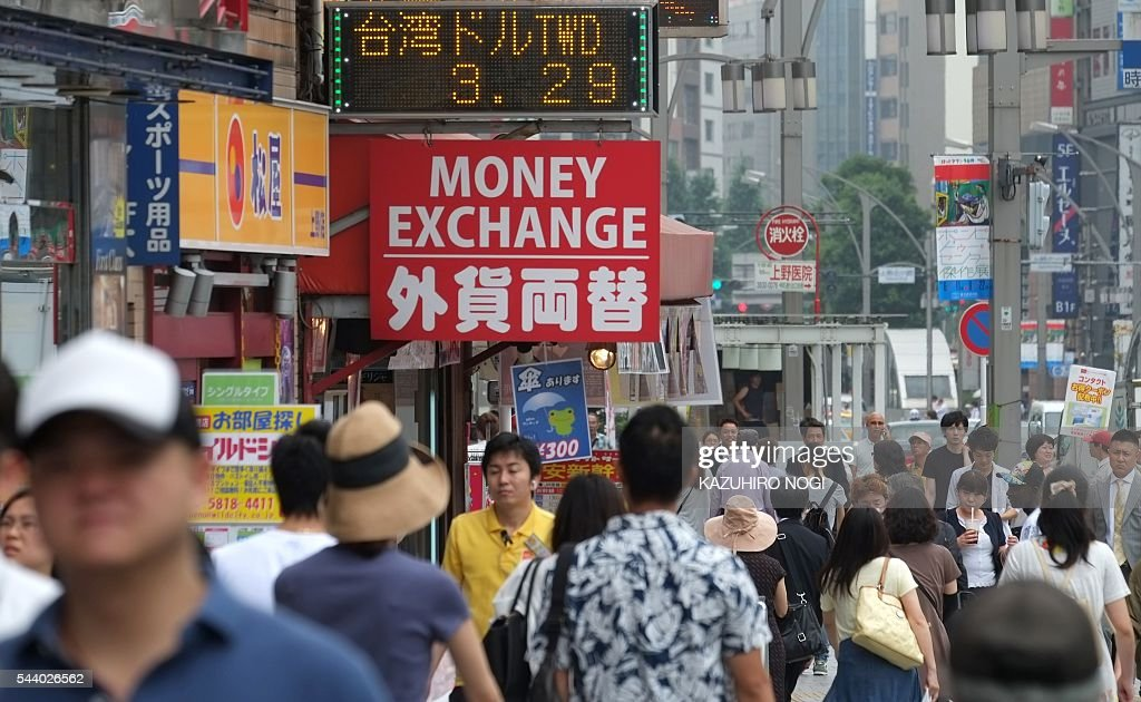 People walk on a street in Tokyo on July 1, 2016. Japan was clobbered with a one-two punch July 1 morning as weak data and a lacklustre business confidence report underscored the slowdown dragging on the world's number three economy. / AFP / KAZUHIRO
