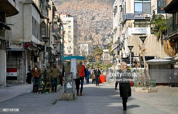 People walk on a street on January 24 2015 in Damascus Syria Syria is torn apart by ProBashar alAssad AntiBashar alAssad and Islamic State