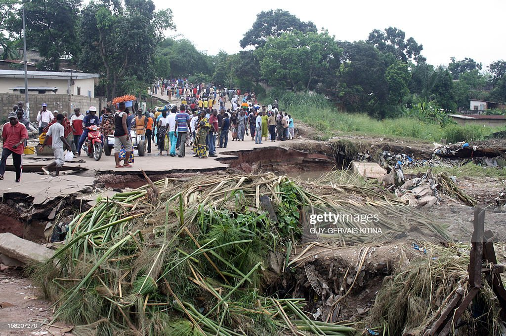 People walk on a street partially destroyed during a flood caused by torrential rains, on December 11, 2012 in Brazzaville. At least 13 people died in the Republic of Congo and two dozen others were injured after this flood caused homes to collapse in southern Brazzaville over the weekend, authorities said on December 10.