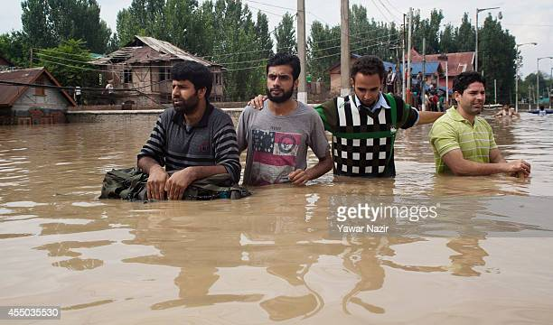 People walk on a submerged road in a flooded area on September 09 2014 in Srinagar the summer capital of Indian administered Kashmir India Kashmir...