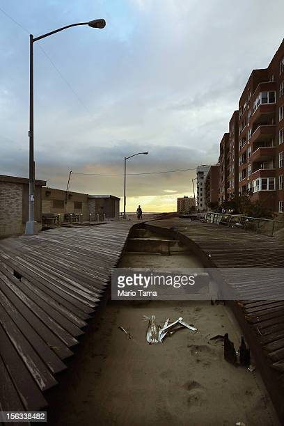 People walk on an area of boardwalk that split during Superstorm Sandy in the Rockaway neighborhood on November 13 2012 in the Queens borough of New...