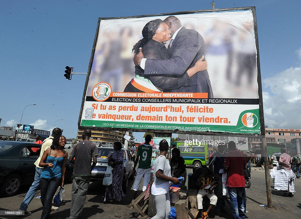 People walk on April 18, 2013 in the Abidjan popular district of Treichville under a poster of the Ivorian independent electoral commission (CEI) reading 'If you lost the election today, congratulate the winner, your turn will come tomorrow.' published. The party of Ivorian President Alassane Ouattara on April 17, 2013 voiced concern over growing political tension ahead of local polls meant to cement post-conflict stabilisation. AFP PHOTO / SIA KAMBOU