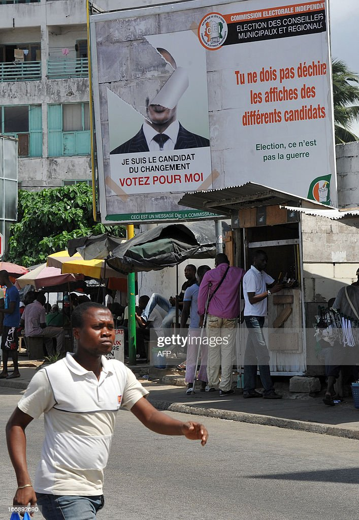 People walk on April 18, 2013 in the Abidjan popular district of Treichville under a poster of the Ivorian independent electoral commission (CEI) reading 'You must not tear campaign posters of other candidates'. The party of Ivorian President Alassane Ouattara on April 17, 2013 voiced concern over growing political tension ahead of local polls meant to cement post-conflict stabilisation. AFP PHOTO / SIA KAMBOU