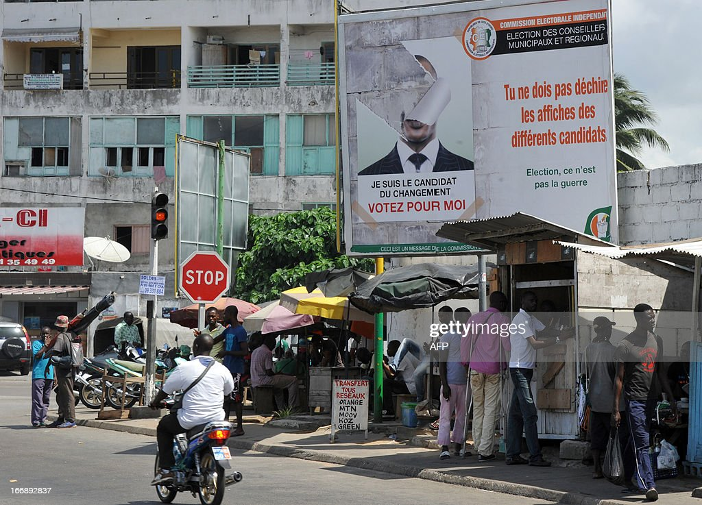 People walk on April 18, 2013 in the Abidjan popular district of Treichville under a poster of the Ivorian independent electoral commission (CEI) reading 'You must not tear campaign posters of other candidates'. The party of Ivorian President Alassane Ouattara on April 17, 2013 voiced concern over growing political tension ahead of local polls meant to cement post-conflict stabilisation.