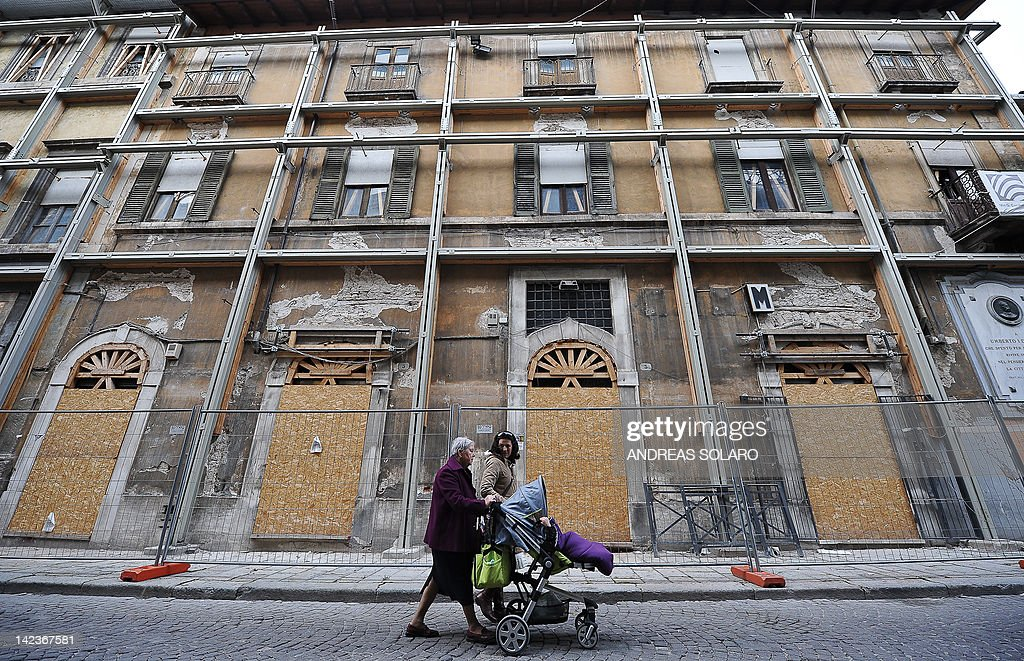 People walk on April 2 2012 in a street near the 'red zone' closed to public in the historic area of L'Aquila devastated three years ago by an...