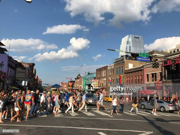 People walk on Broadway Avenue in Nashville Tennessee on August 19 2017 / AFP PHOTO / Daniel SLIM