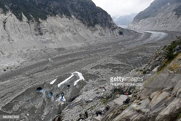 People walk on footbridges as they visit 'La Grotte de glace' on June 8 2015 on the 'Mer de Glace' glacier in ChamonixMontBlanc French Alps At 7km...
