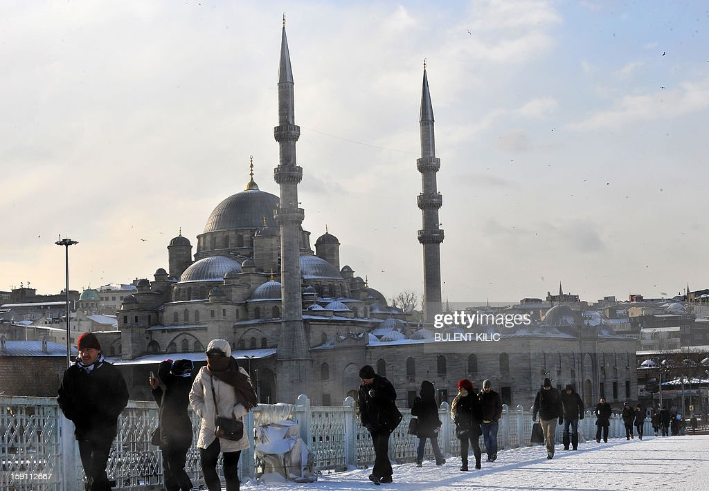 People walk on Galata Bridge covered with snow in Istanbul, on January 8, 2013. Heavy snowfall blanketed Turkey's commercial hub Istanbul, a city of 15 million, paralysing daily life, disrupting air traffic and land transport. Officials said the snow is expected to continue until late tomorrow, according to the weather forecast. AFP PHOTO / BULENT KILIC