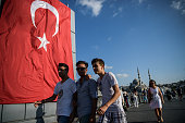 People walk on Galata bridge next to a giant Turkish national flag at Eminonu district on July 26 2016 in Istanbul following the failed military coup...