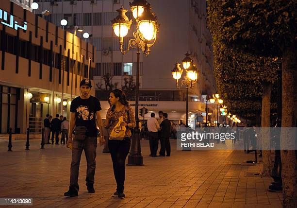 People walk on Habib Bourguiba avenue after an overnight curfew imposed on the Tunisian capital this month after several days of unrest has been...