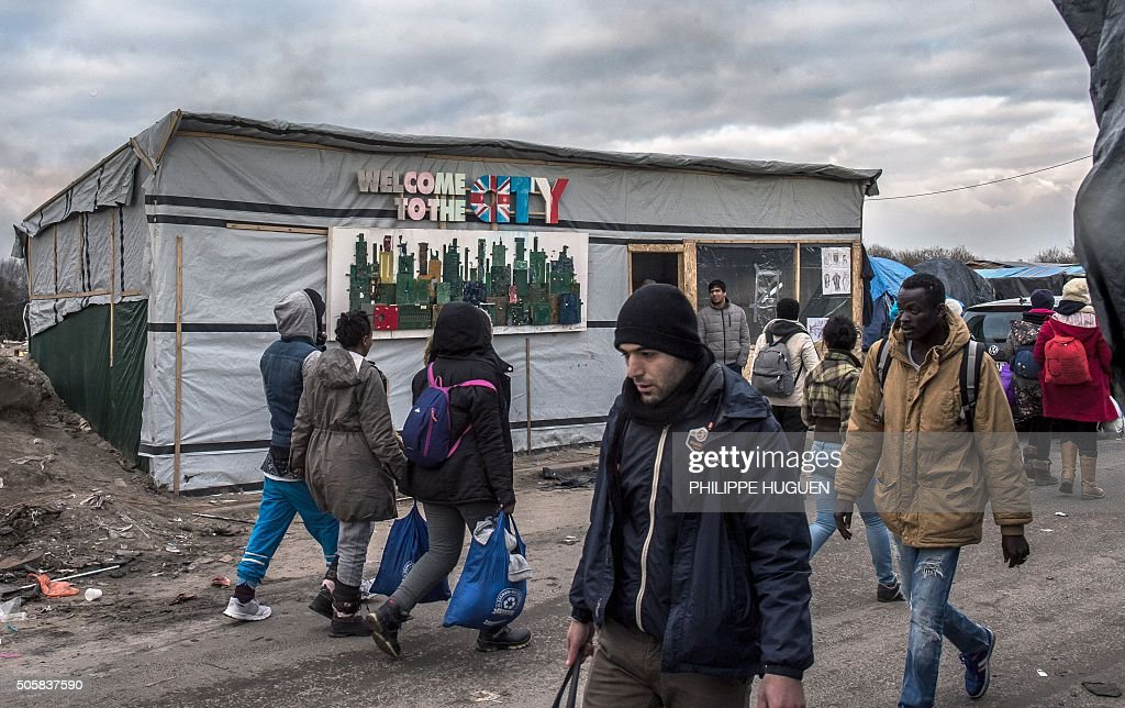 People walk on January 20 in the migrant shantytown on the outskirts of Calais known as the 'Jungle' where thousands are trying to make their way...