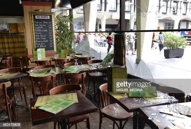 People walk on July 21 in Sarcelles a northern Paris suburb near a restaurant of a shopping center in Les Flanades neighborhood damaged on July 20...