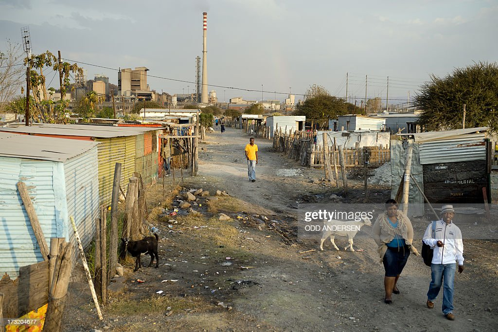 People walk on July 9, 2013 in the Nkaneng shantytown next to the platinum mine, run by British company Lonmin, in Marikana. On August 16, 2012, police at the Marikana mine open fire on striking workers, killing 34 and injuring 78, during a strike was for better wages and living conditions. Miners still live in dire conditions despite a small wage increase. AFP PHOTO / ODD ANDERSEN