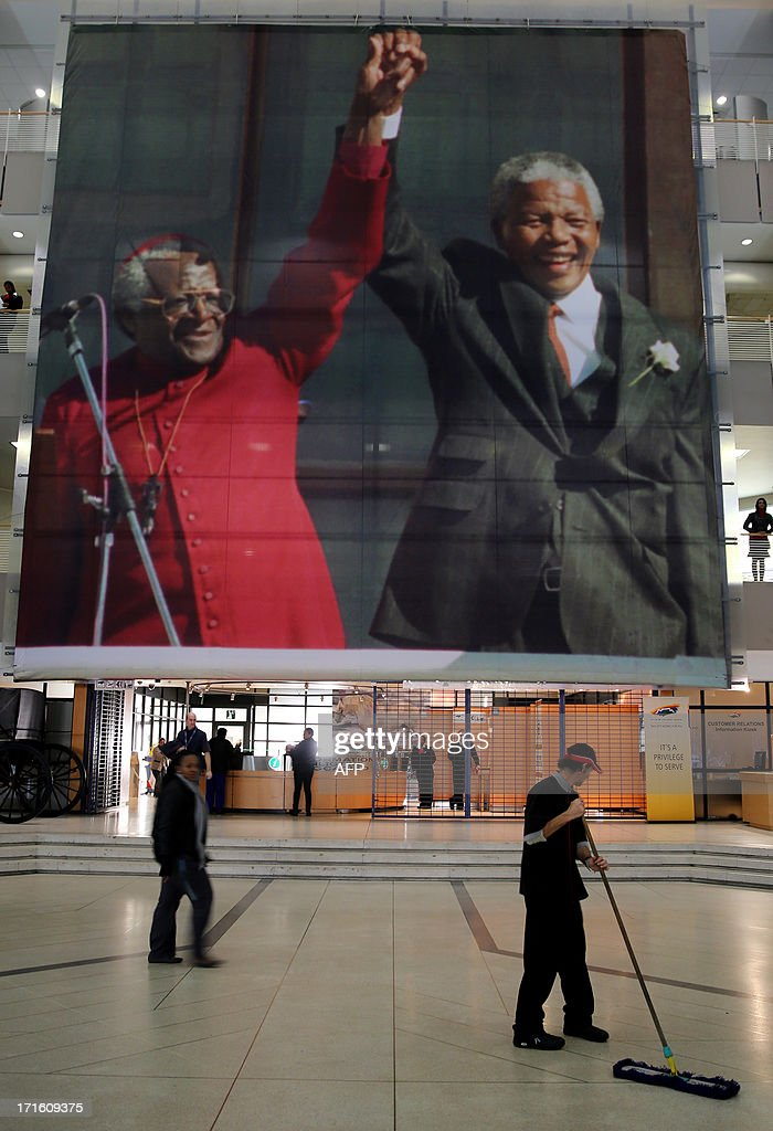 People walk on June 27, 2013 past a giant picture of former South African President Nelson Mandela (R) and Archbishop Desmond Tutu at the Cape Town Civic Center in the center of Cape Town. As South Africans prayed for the anti-apartheid hero who defeated decades of racist white minority rule to became the country's first black president, President Jacob Zuma late on June 26 abruptly cancelled a trip to Mozambique after he visited the hospital where Mandela is critically ill. It is the first time Zuma has scrapped a public engagement since Mandela was hospitalized nearly three weeks ago.