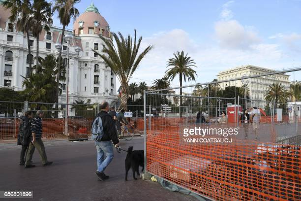 People walk on March 22 2017 on the seafront Promenade des Anglais in Nice southeastern France where bollards and fences are installed to prevent any...