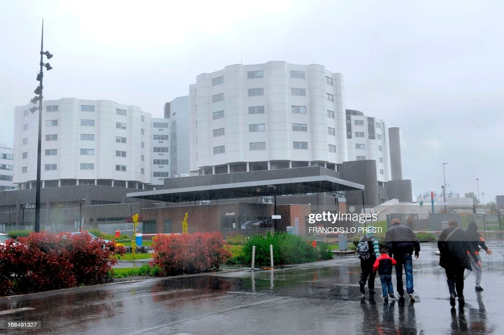 People walk on May 10, 2013 in front of the 'Jean-Bernard' hospital in Valenciennes, where the first French person infected by a new SARS-like virus arrived on April 23, before being transferred to Douai and Lille. French health authorities said on May 10 they suspected a third person of being infected after coming into contact with a man confirmed to be suffering from a new SARS-like virus that has killed 18 people, mostly in Saudi Arabia. AFP PHOTO / FRANCOIS LO PRESTI
