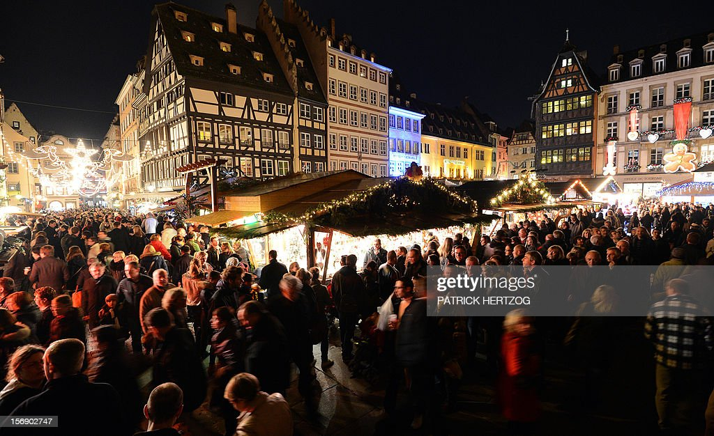 People walk on November 24, 2012 in Strasbourg, eastern France on the opening day of the city's Christmas market, the largest and one of the eldest French Christmas markets. With over 300 market chalets, Strasbourg attracts over 1.6 million visitors during the Christmas season. AFP PHOTO / PATRICK HERTZOG