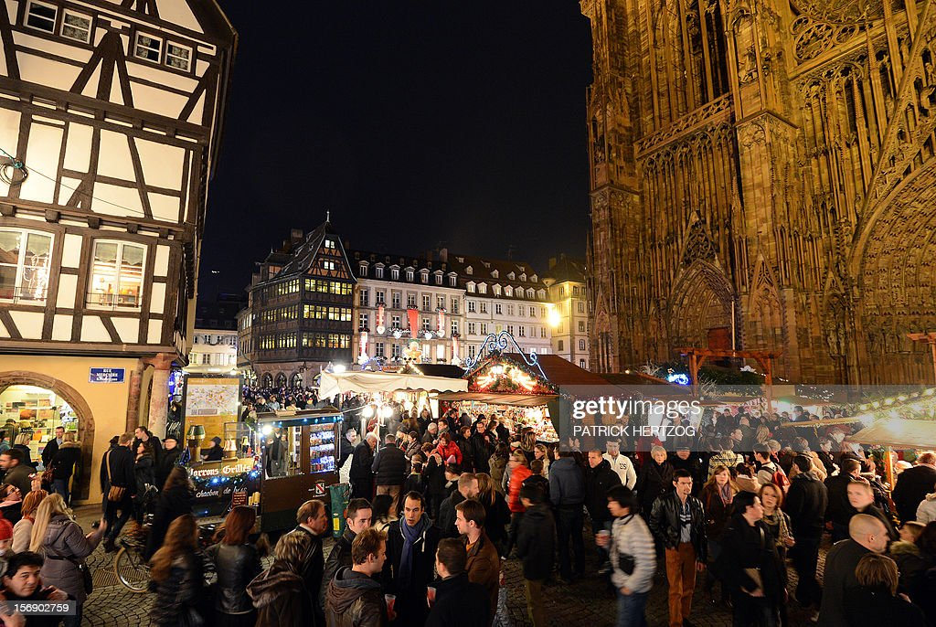 People walk on November 24, 2012 in Strasbourg, eastern France on the opening day of the city's Christmas market, the largest and one of the eldest French Christmas markets. With over 300 market chalets, Strasbourg attracts over 1.6 million visitors during the Christmas season.