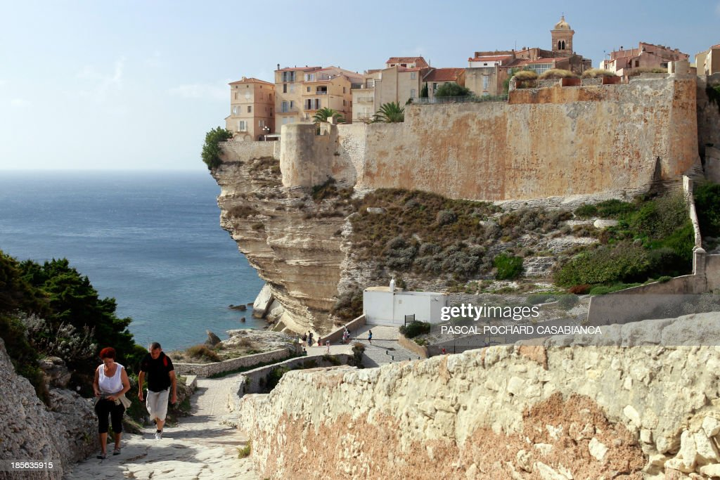 People walk on October 22, 2013 near the old city of Bonifacio, France's southern Mediterranean island of Corsica. Bonifacio is classified as one of France's most beautiful villages.