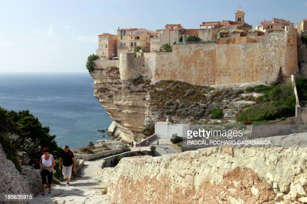 People walk on October 22 2013 near the old city of Bonifacio France's southern Mediterranean island of Corsica Bonifacio is classified as one of...
