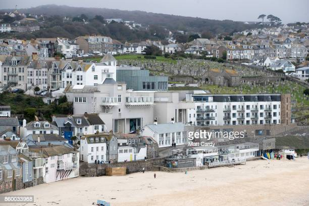 People walk on Porthmeor Beach in front of the exterior of the Tate St Ives which is set to reopen to the public this weekend after a fouryear £20...