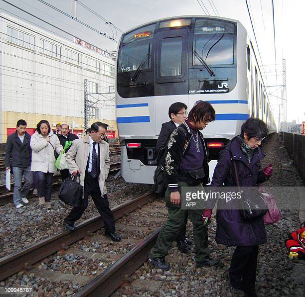 People walk on railway tracks as commuter train services have been stopped in Funabashi city suburban Tokyo on March 11 2011 A massive 89magnitude...