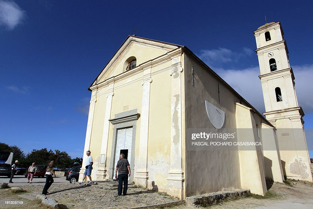 People walk on September 19, 2013, in front of a church in San Antonino on the French Mediterranean island of Corsica. San Antonino is listed as one of the most beautiful villages of France.