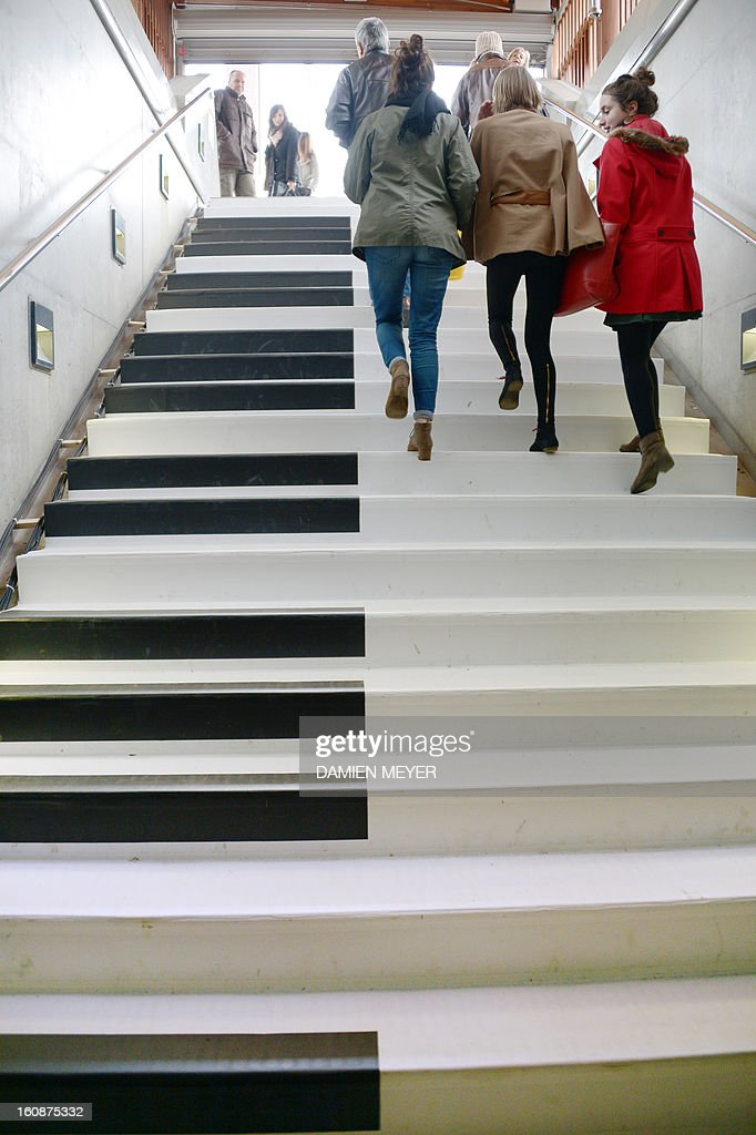 People walk on subway stairs turned into a musical keyboard on February 7, 2013 in Rennes, western France. For each step a musical note sounds, turning walk into melody. This device, set by 'les jardins numériques' is available until next Sunday. Car firm Volkswagen did this in Stockholm in 2009. AFP PHOTO/ DAMIEN MEYER