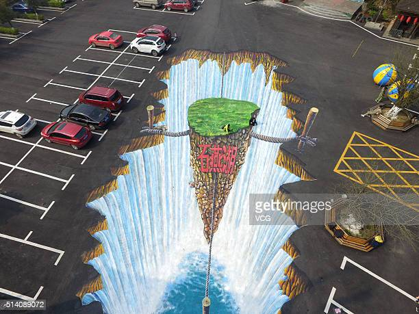 People walk on the 3D painting on the ground of a parking lot at the Shiyan Lake on March 6 2016 in Changsha Hunan Province of China The 3D painting...