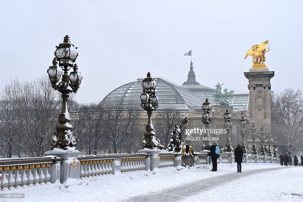 People walk on the Alexandre III bridge on January 19, 2013 in Paris, after the snow fell over the French capital overnight.