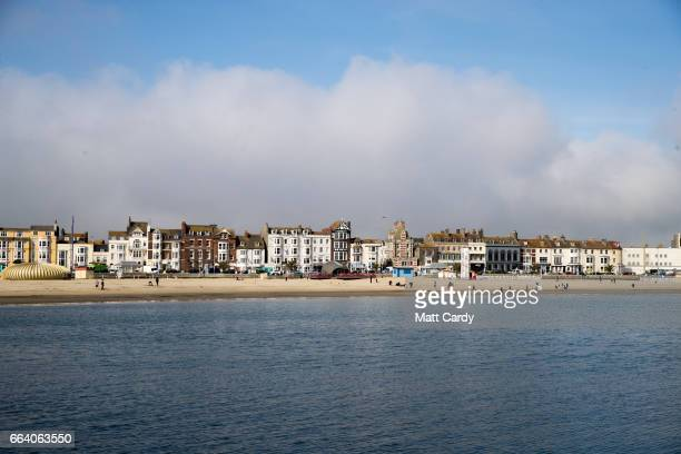 People walk on the beach as sea mist rolls in from the sea at Weymouth as the resort prepares for the start of the holiday season on April 3 2017 in...