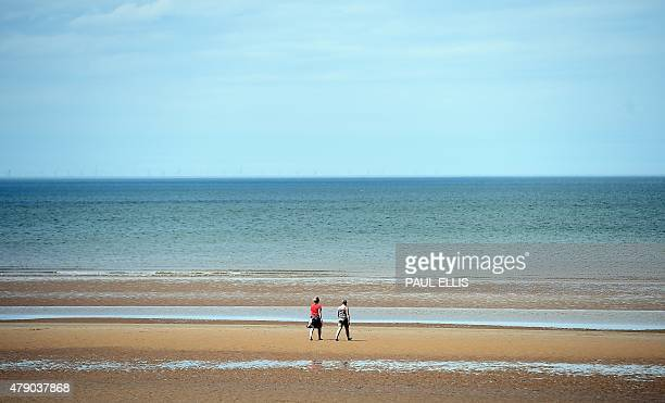 People walk on the beach at New Brighton in northwest England on June 30 2015 Temperatures soared above 40 degrees in Spain and Portugal on Monday...