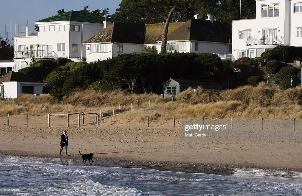 People walk on the beach in the exclusive residential area of Sandbanks on January 17 in Poole England Before the credit crunch properties built on...