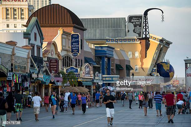People walk on the boardwalk in Atlantic City New Jersey US on Thursday July 17 2014 Once the East Coast's gambling hub Atlantic City has suffered as...