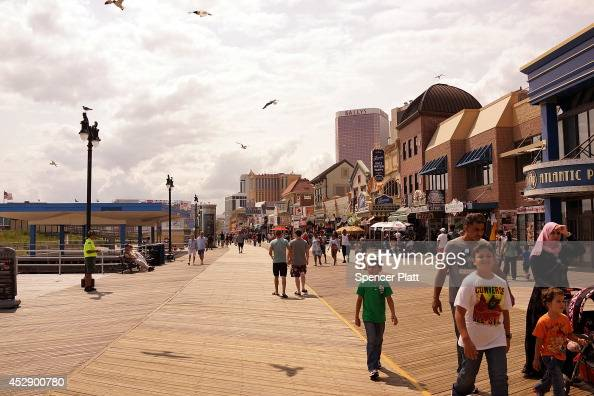 People walk on the boardwalk in Atlantic City on July 29 2014 in Atlantic City New Jersey Since January of 2014 four of Atlantic City's 11 casinos...