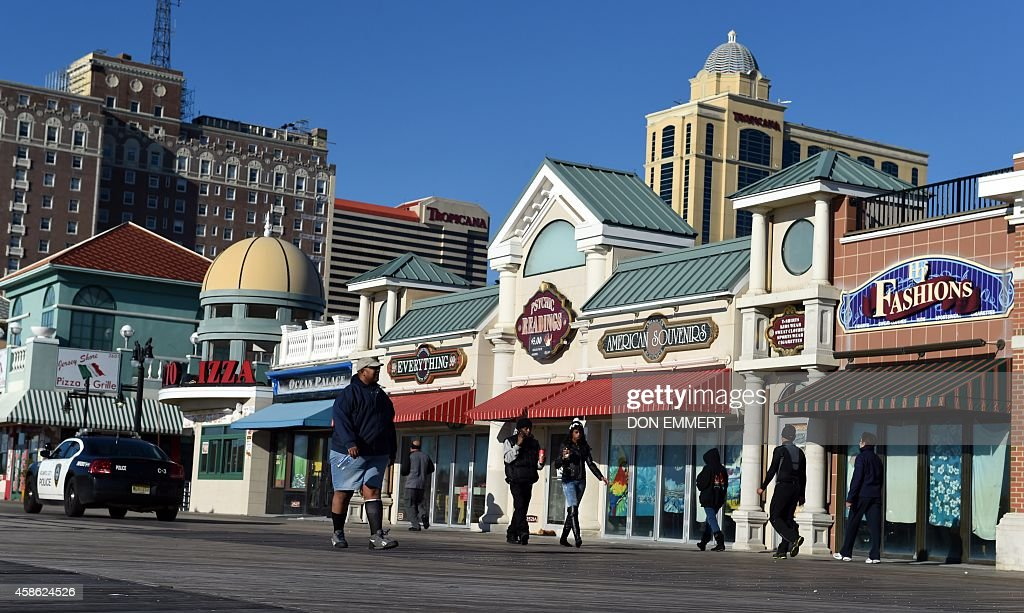 People walk on the boardwalk November 8 2014 in Atlantic City New Jersey AFP PHOTO/Don Emmert