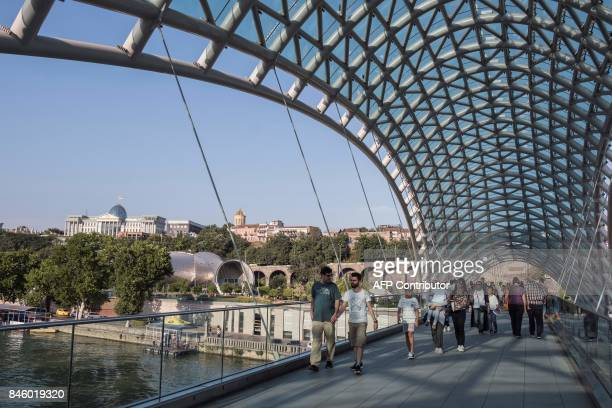 People walk on the 'Bridge of Peace' over the Kura river in downtown Tbilisi on August 9 2017 / AFP PHOTO / JOEL SAGET