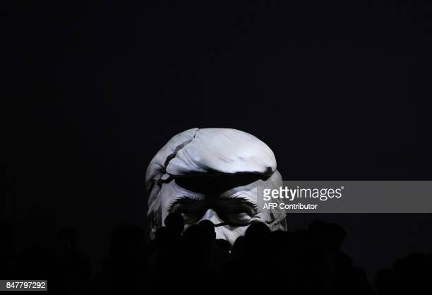 TOPSHOT People walk on the catwalk in front of a cracked bust representing US president Donald Trump after the presentation of Ana Locking's...